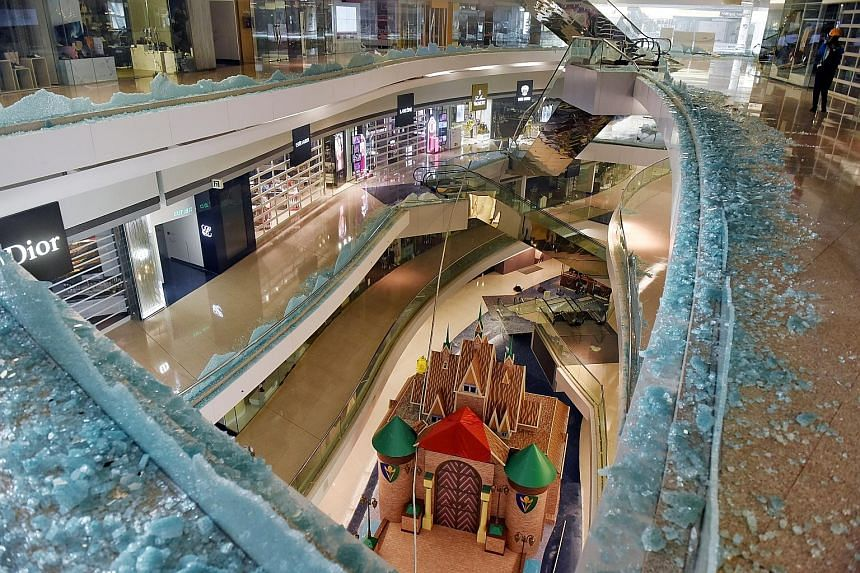 The Festival Walk shopping mall (left) was among businesses vandalised during protests in Kowloon Tong, Hong Kong, last Wednesday. On Tuesday, some stores in the city, such as this (centre), were set on fire. Others, like Starbucks, were hit after a