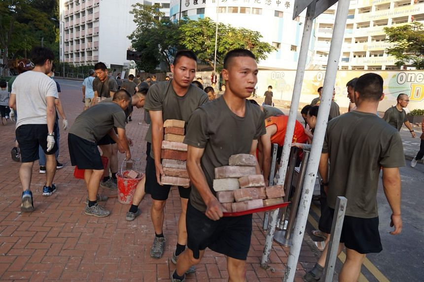 Personnel from the PLA barracks in Hong Kong help clean up the city streets on Nov 16, 2019.