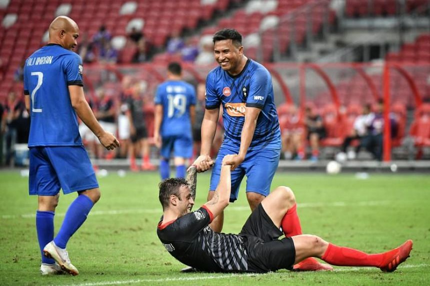 Manchester Reds' Dimitar Berbatov is helped up by Singapore Reds' Alam Shah during their Battle of the Reds match at the National Stadium on Nov 16, 2019.