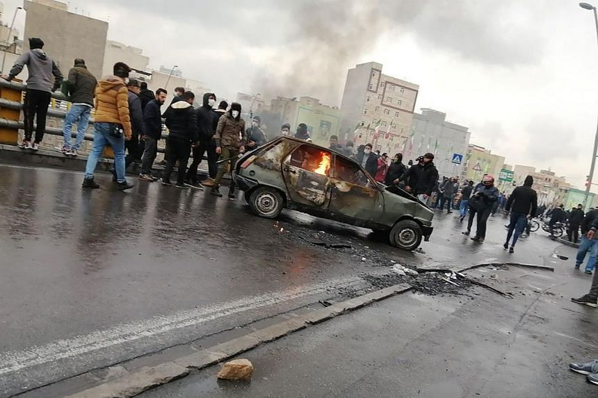 Iranian protesters gather around a burning car during a demonstration against an increase in gasoline prices in the capital Teheran.