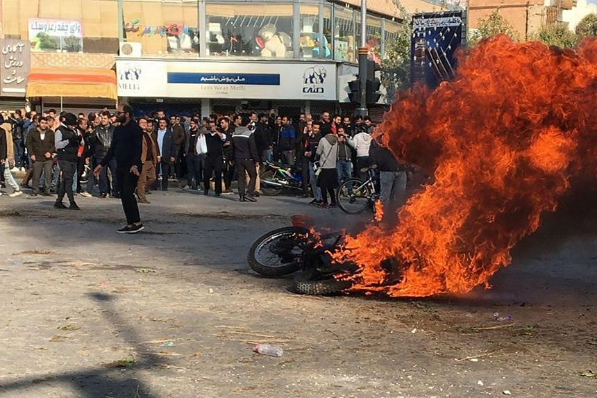 Iranian protesters gather around a burning motorcycle during a demonstration against an increase in gasoline prices in the central city of Isfahan.