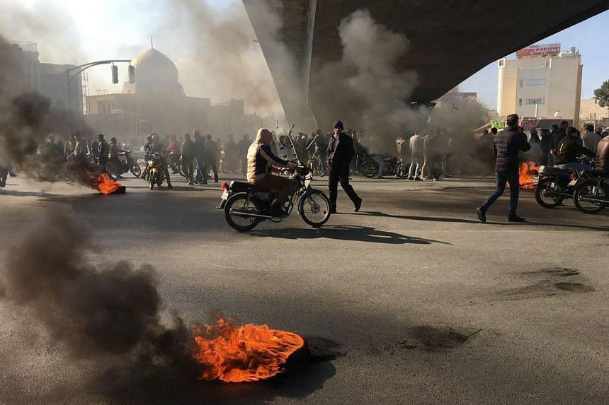 Iranian protesters rally amid burning tires during a demonstration against an increase in gasoline prices, in the central city of Isfahan.