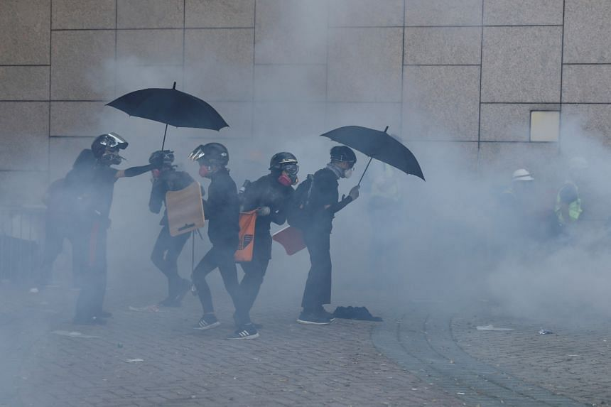 Protesters stand with gas masks amidst tear gas during clashes with police outside Hong Kong Polytechnic University in Hong Kong on Nov 17, 2019.