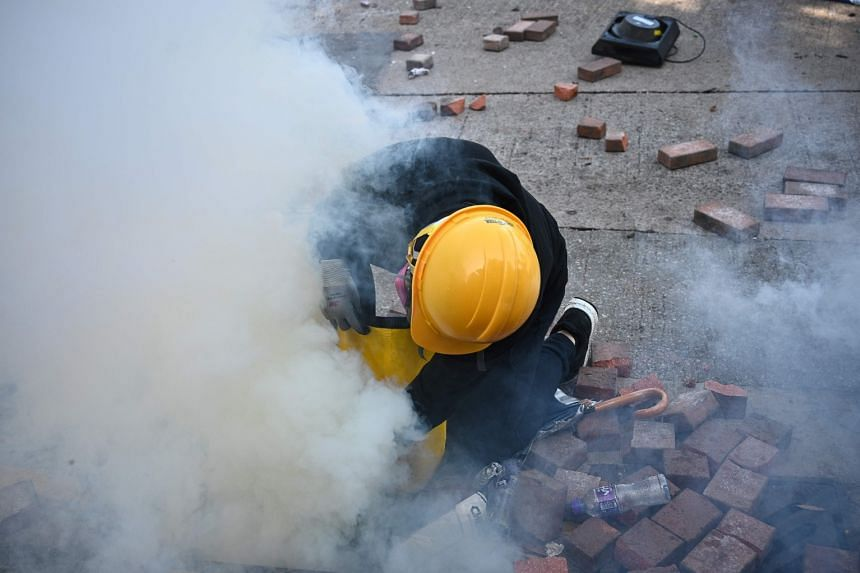 A protester attempts to snuff out a tear gas canister fired by police outside the Hong Kong Polytechnic University in Hong Kong on Nov 17, 2019.