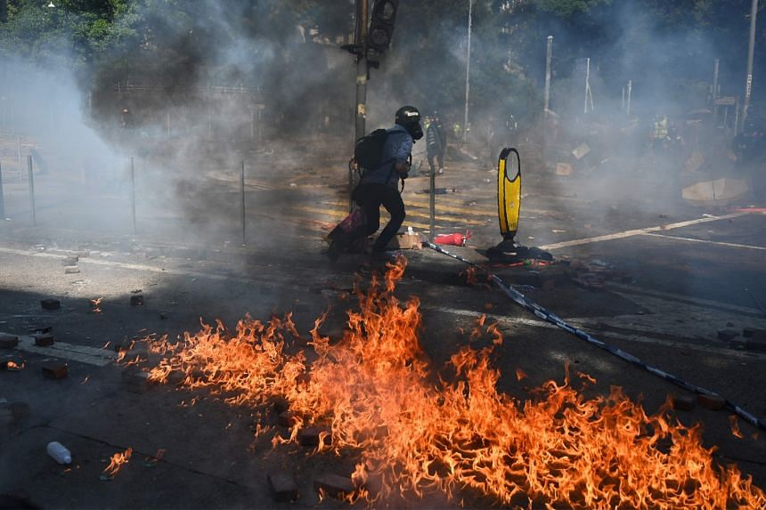 A journalist runs past a fire from a molotov cocktail thrown by protesters after police fired tear gas outside the Hong Kong Polytechnic University in Hong Kong on Nov 17, 2019.
