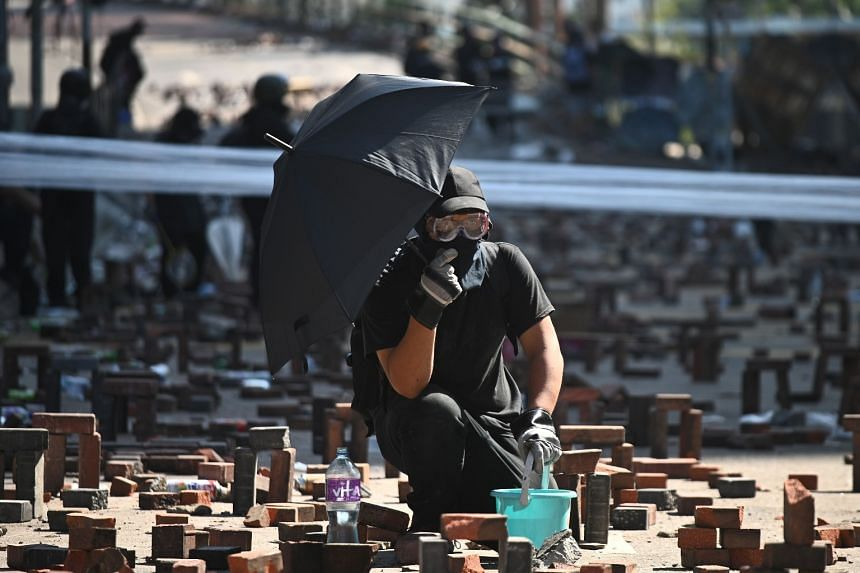 A protester holding an umbrella crouches amid brick obstacles after police fired tear gas outside the Hong Kong Polytechnic University in Hong Kong on Nov 17, 2019.