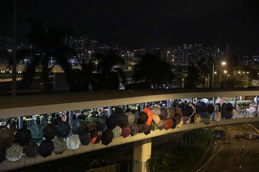 Protesters stand on a bridge during clashes with the police outside the Polytechnic University, in Hong Kong, on Nov 17, 2019.