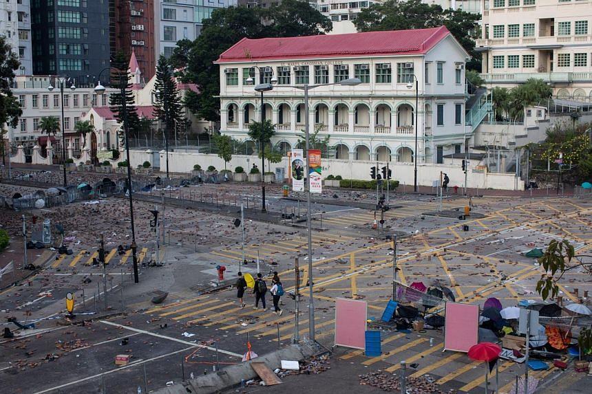 Pedestrians cross an intersection littered with debris and bricks near the Hong Kong Polytechnic University in Hong Kong, on Nov 17, 2019.
