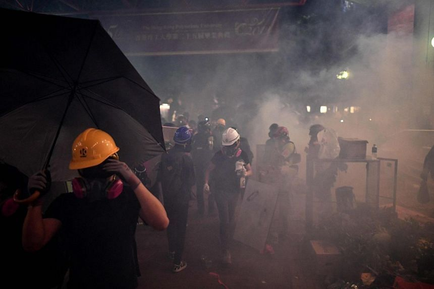 Protestors stand amidst tear gas thrown by police during clashes at the Polytechnic University of Hong Kong in Hung Hom district of Hong Kong, on Nov 16, 2019.