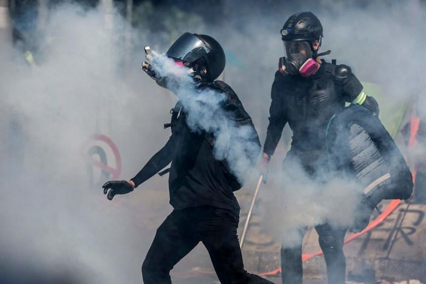 A protester throwing a tear gas pellet back at the police during a clash outside the Hong Kong Polytechnic Univeristy on Nov 17, 2019.