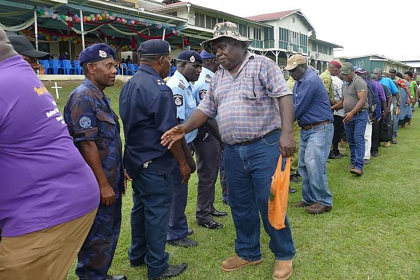 "Former Bougainville Revolutionary Army fighters greeting Papua New Guinea policemen on Nov 6 in Kokopo, East New Britain, at a reconciliation ceremony in a symbolic outpouring of forgiveness between ""Melanesian brothers"" ahead of a historical independence"