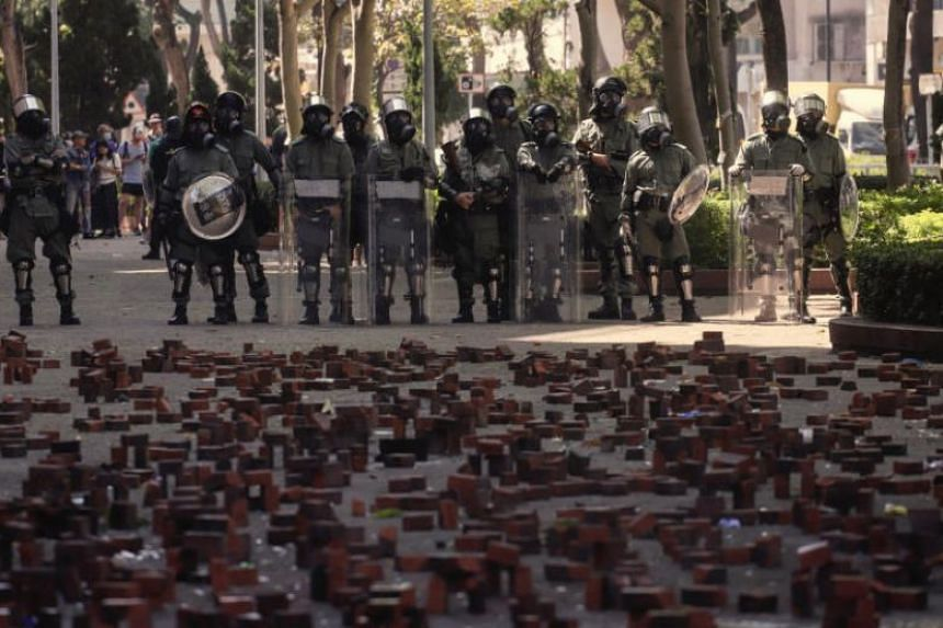 Hong Kong's riot police stand in front of bricks stuck to a road by anti-government protesters to stop their advancement outside Hong Kong Polytechnic University on Nov 17, 2019.
