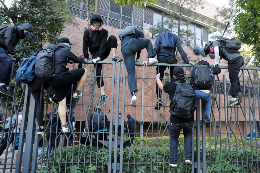 Protesters climb a fence at the Hong Kong Polytechnic University as they fail to leave the area after they came under tear gas attacks by police during clashes in Hong Kong on Nov 18, 2019.