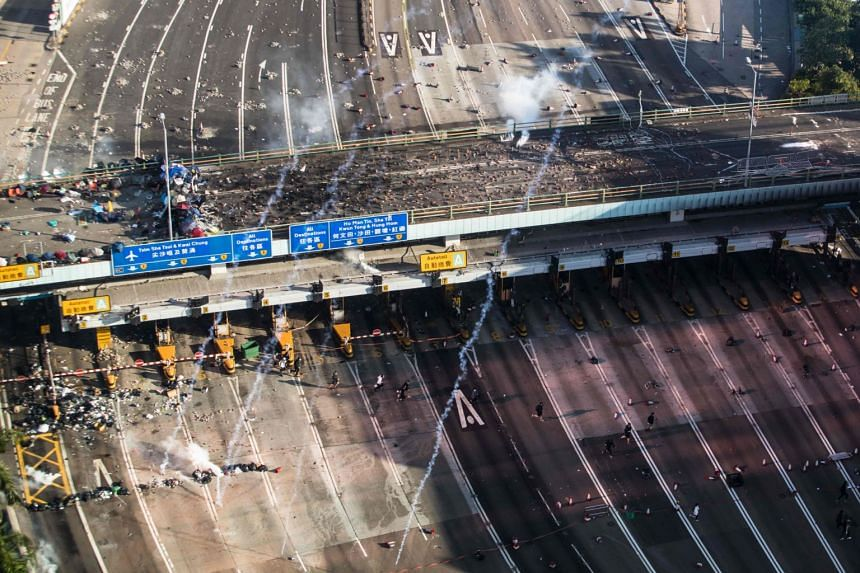 Police fire tear gas as protesters run on a road leading to the Cross Harbour Tunnel while trying to leave Hong Kong Polytechnic University in Hong Kong on Nov 18, 2019.