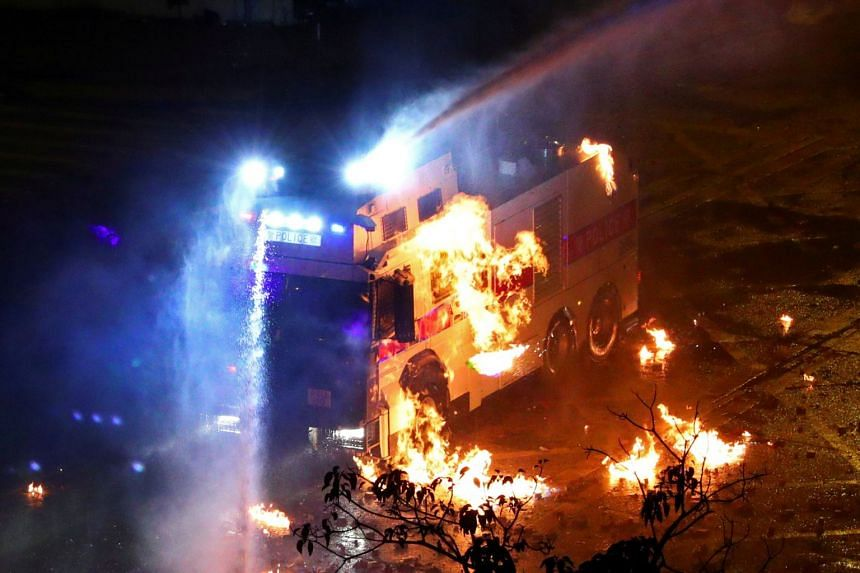 A riot police vehicle is set on fire during clashes outside Hong Kong Polytechnic University, on Nov 18, 2019.