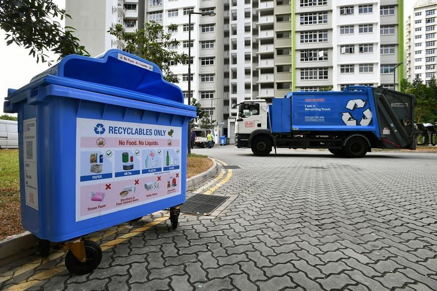 Recycling bin with new recycling bin label and Blue Recycling Truck below Blk 524A Tampines Central 7 on Aug 29, 2019.