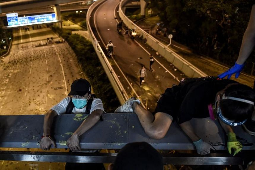 Protesters take a rope down from a bridge to a highway, to escape from Hong Kong Polytechnic University campus and from police in Hong Kong on Nov 18, 2019.