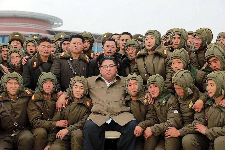 An undated photo released by the Korean Central News Agency showing North Korean leader Kim Jong Un with members of the Air and Anti-Aircraft Force of the Korean People's Army. PHOTO: