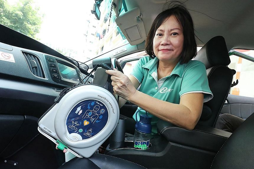 HDT taxi driver Vicky Lim with an automated external defibrillator. Sponsorship from the Singapore Heart Foundation has allowed the cab company to fit 50 of its taxis with the portable device, which can send an electric shock to the heart to revive i