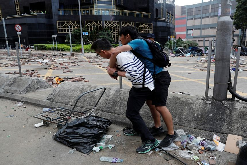 A man carries his son outside the Hong Kong Polytechnic University campus as they wait for an ambulance during protests in Hong Kong on Nov 19, 2019.
