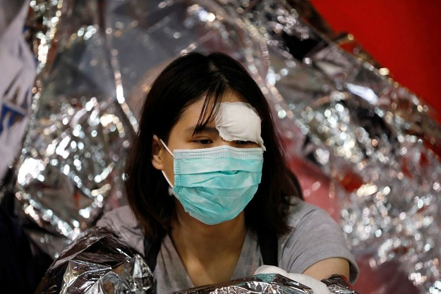 A protester sits inside the Hong Kong Polytechnic University campus as she waits for a medical team to take her to hospital  on Nov 19, 2019.