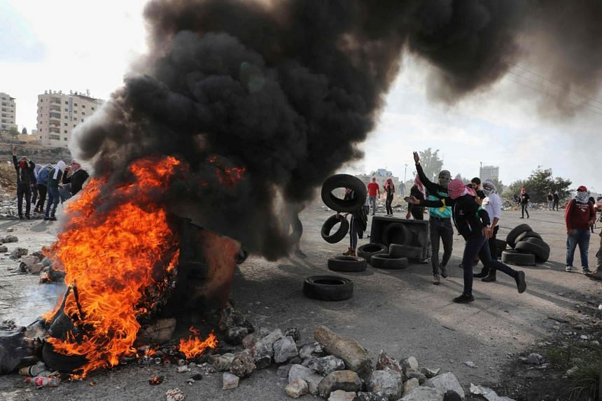 Palestinian protesters burn tires amid clashes with Israeli security forces following an anti-Israel demonstration at the entrance of the West Bank city of Ramallah near the Jewish settlement of Beit El, on Nov 16, 2019.