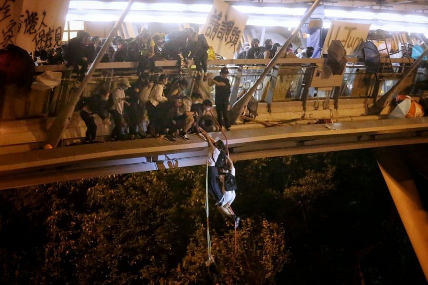 Anti-goverment protesters who were inside Hong Kong Polytechnic University abseil onto a highway during a police siege of the campus in Hong Kong on Nov 18, 2019.