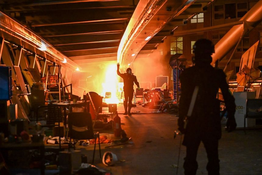 An anti-government protester walks past fire on a bridge at one of the entrances to Hong Kong Polytechnic University, on Nov 19, 2019.