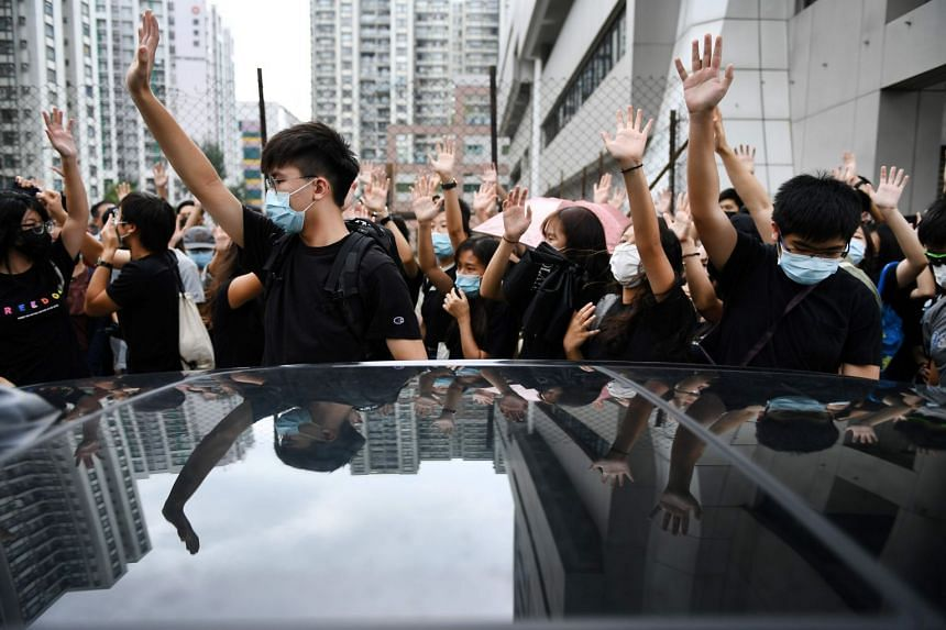 Protesters shout slogans as they gather outside the Eastern District Courts in Hong Kong, where the first protesters arrested for wearing face masks appeared in court on Oct 7, 2019.