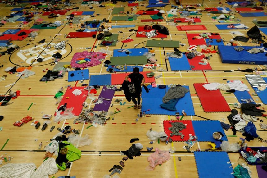 A protester looks for clothes in a gym hall which served as a sleeping area on the campus of the Hong Kong Polytechnic University on Nov 19, 2019.
