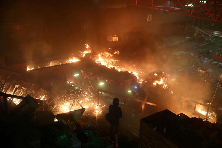 A protester looks at fires at Hong Kong Polytechnic University during an anti-government protest in Hong Kong on Nov 18, 2019.