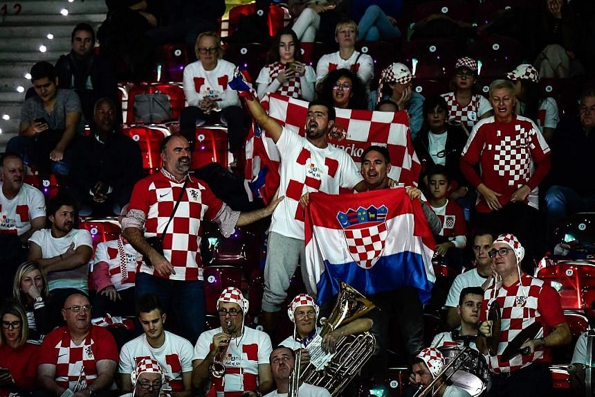 Croatia's Ivan Dodig and Nikola Mektic playing Russia's Karen Khachanov and Andrey Rublev during their doubles tie in Madrid on Monday. While some supporters, including this group from Croatia (above), turned up to cheer the players, the stands were
