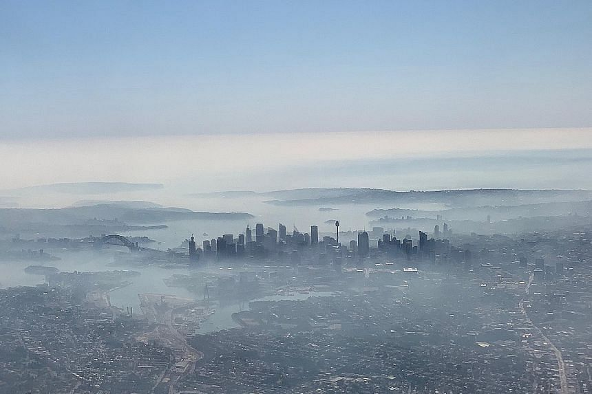 Sydney's skyline obscured by haze yesterday, as seen from a plane. Much of the smoke is being blown from a huge bush fire spreading across two national parks that is just 100km north-west of central Sydney at its closest point.