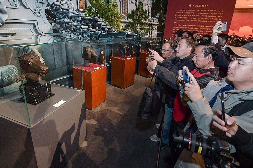 Visitors viewing the bronze horse head looted from the Old Summer Palace by Anglo-French allied forces in 1860 at an exhibition in Beijing last week.