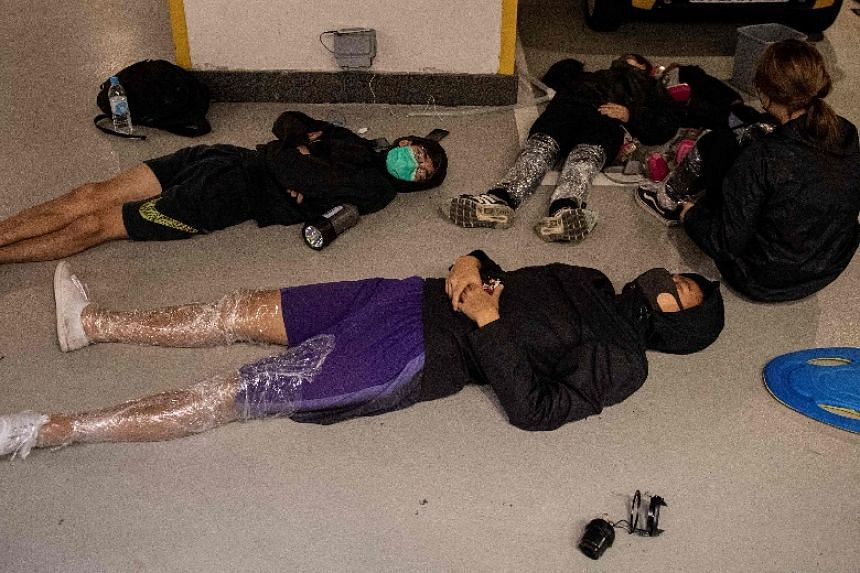 Protesters sleep on the floor of a parking lot inside the Hong Kong Polytechnic University on Nov 20, 2019.