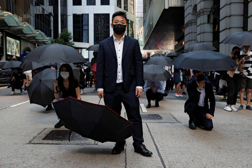 Office workers hold umbrellas as they attend a flash mob anti-government protest after police fired tear gas at the financial Central district in Hong Kong on Nov 11, 2019.