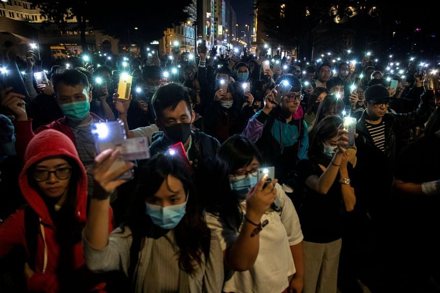 Protesters raise their mobile phones as they gather to show their support for protesters in the Hong Kong Polytechnic University campus on Nov 19, 2019.