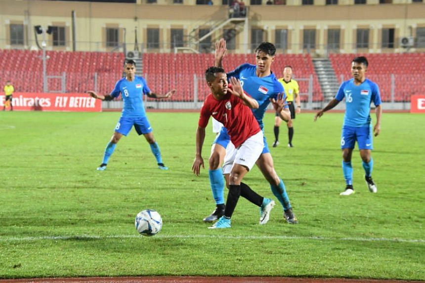 Singapore striker Ikhsan Fandi (centre right) tussles with Yemen's Ahmed Al-Sarori in the Lions 2-1 win in a World Cup Qualifier in Bahrain.