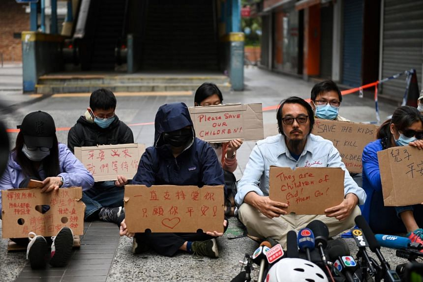 Family members of students barricaded inside Hong Kong Polytechnic University hold up signs during a protest near the campus in Hong Kong on Nov 19, 2019.