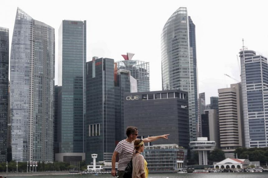 In a photo taken on Nov 19, a couple gesture while pictured against the skyline of the financial district in Singapore.