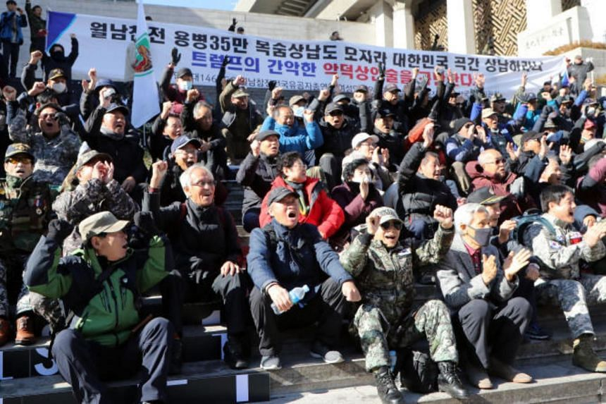 A photo taken on Nov 20 shows South Korean Vietnam War veterans denouncing US President Donald Trump's demand for the increase of the South Korean share of costs for stationing US Forces Korea.