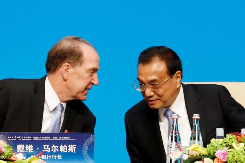 """World Bank President David Malpass (left) speaks with Chinese Premier Li Keqiang before a news conference following the """"1+6"""" Roundtable meeting at the Diaoyutai state guesthouse in Beijing on Nov 21, 2019."""