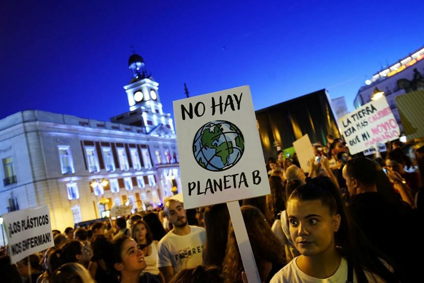 In a photo from Sept 27, 2019, a woman holds a placard during a protest demanding global politicians urgent actions to fight climate change in Madrid.