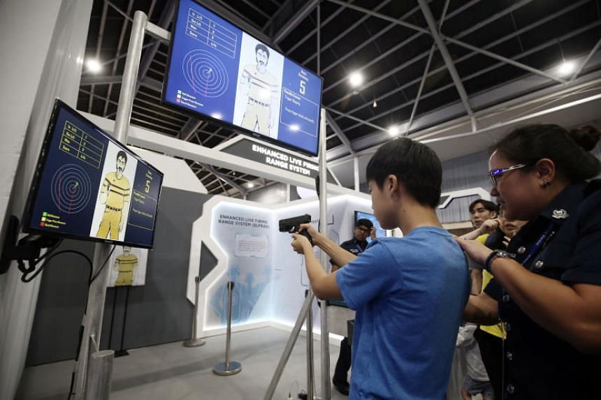 Visitors can try their hand at a Glock pistol firing simuluation with the Enhanced Live Firing Range System at the Singapore Police Force's booth.