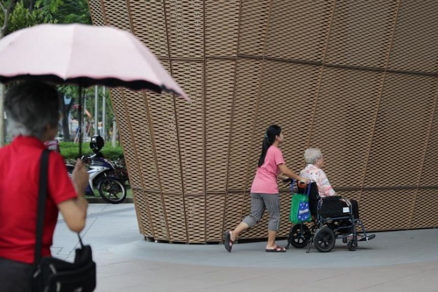 A domestic helper pushing an elderly woman on the wheelchair at HeartBeat@Bedok on Nov 5, 2019.