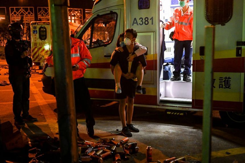 A man carries an injured woman to an ambulance as some protesters leave the Hong Kong Polytechnic University on Nov 19, 2019. Arrests and interrogations of suspects in public hospital rooms have become commonplace.