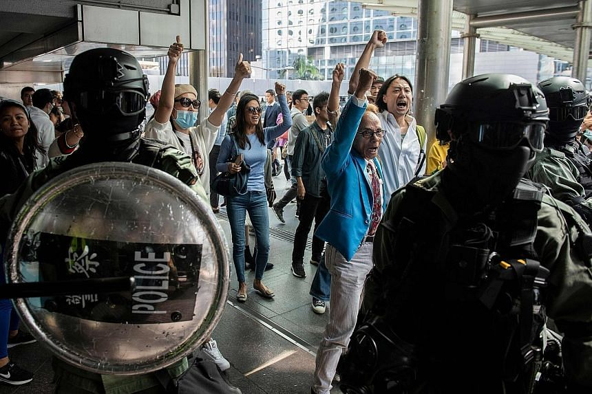 Riot police on the alert as pro-China supporters shouted slogans and gestured towards office workers (not seen in picture) who had gathered in support of pro-democracy protesters yesterday during a lunchtime rally in Hong Kong's Central district.