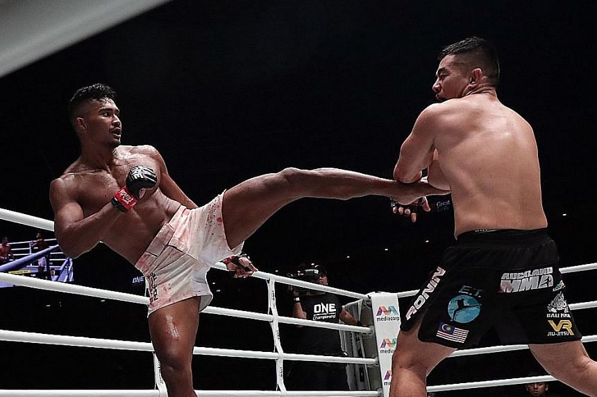 Singapore's Amir Khan landing a kick at Malaysia's Ev Ting in One Championship's Edge of Greatness event at the Indoor Stadium last night. Amir won for the first time in four bouts.