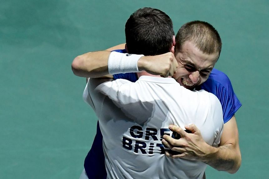 Britain's Daniel Evans celebrates with captain Leon Smith after winning the singles quarter-final against Germany's Jan-Lennard Struff.