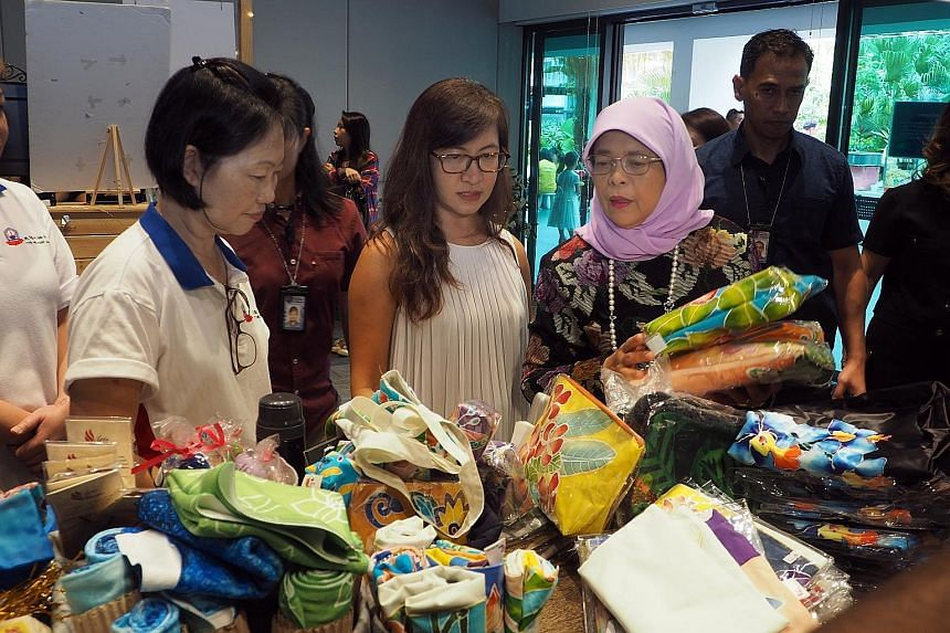 President Halimah Yacob viewing a product by Arts@Metta at i'mable Collective's gift market at the Enabling Village in Lengkok Bahru yesterday. The collective aims to be the preferred first stop for organisations keen to support the purchase of high-